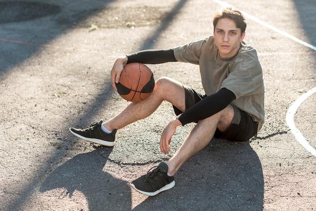 Wysoki widok mężczyzna siedzi na boisko do koszykówki