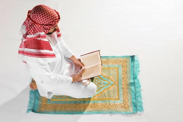 Wysoki widok mężczyzna siedzi na dywaniku modlitwy i czyta