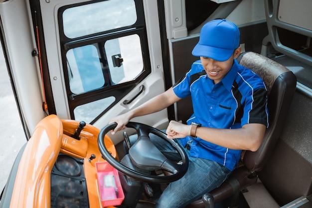 Wysoki widok mężczyzny kierowcy w mundurze, patrząc na zegarek, trzymając kierownicę w autobusie