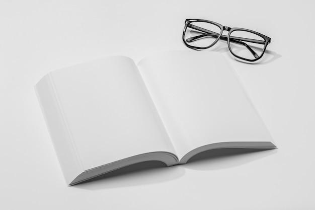 Wysoki widok miejsca na kopię książki z cieniem i okularami