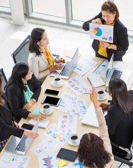 Wysoki widok na sześć kobiet biznesu pracujących i jedną kobietę przedstawiającą wykresy i dokumenty z wykresami z tabletami i laptopami na stole. koncepcja spotkania biznesowego.