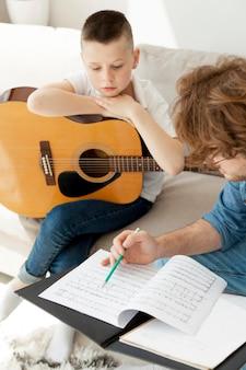 Wysoki widok nauczyciela i chłopiec gra na gitarze