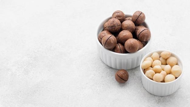 Wysoki widok orzechów makadamia i czekolady w miseczkach