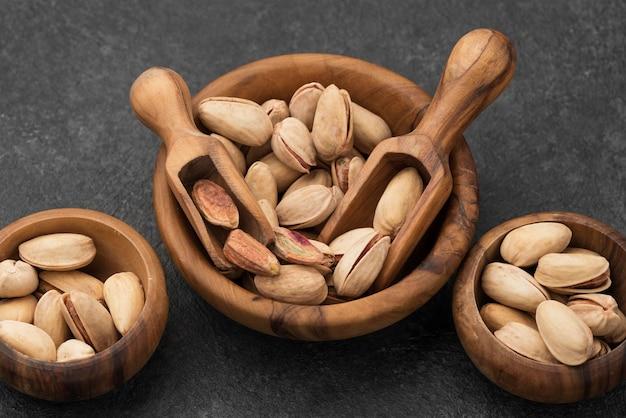 Wysoki widok orzechów pistacjowych w miseczkach z drewnianymi łyżkami