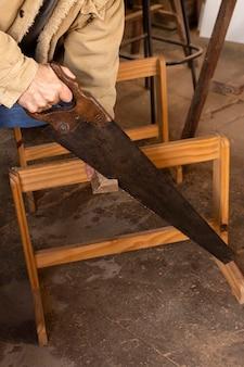 Wysoki widok osoby używającej narzędzia zespołu na drewnie