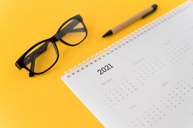 Wysoki widok papeterii kalendarz 2021 na żółtym tle