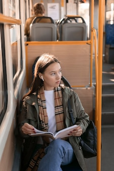 Wysoki widok pasażera, trzymając książkę i odwracając wzrok