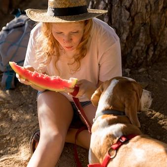 Wysoki widok psa i kobiety jedzącej kawałek arbuza