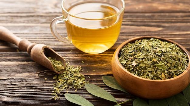 Wysoki widok zielonych liści i filiżankę herbaty
