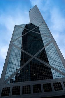 Wysoki wieżowiec w szklanej fasadzie z odbiciem innego wieżowca w hongkongu