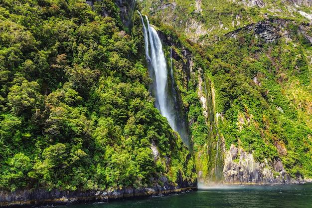 Wysoki wodospad w milford sound, nowa zelandia, zdjęcie zrobione z promu wycieczkowego