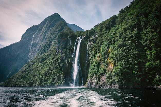 Wysoki wodospad w milford sound, zdjęcie zrobione z promu wycieczkowego.