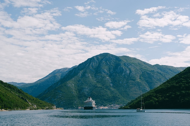 Wysoki, wysoki, ogromny statek wycieczkowy w cieśninie verige, w zatoce boko kotor w czarnogórze, na tle miasta perast