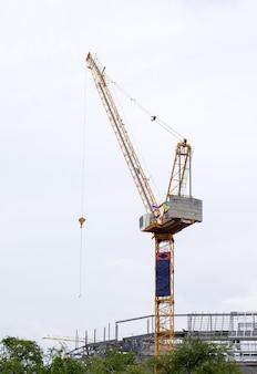 Wysoki żuraw wieżowy na placu budowy do budowy dużego budynku rządowego w obszarze miejskim.