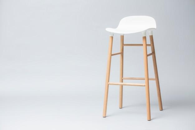 Wysokie białe nogi stołka barowego są drewniane na szarym tle