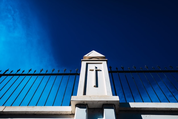 Wysokie, białe ściany betonowe z metalowymi kratami oddzielają zmarłych od zewnętrznego cmentarza