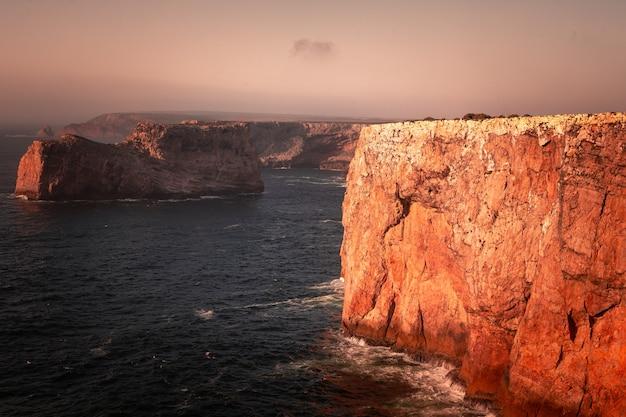 Wysokie czerwone klify wokół przylądka sao vicente na południowo-zachodnim krańcu portugalii, w regionie algarve
