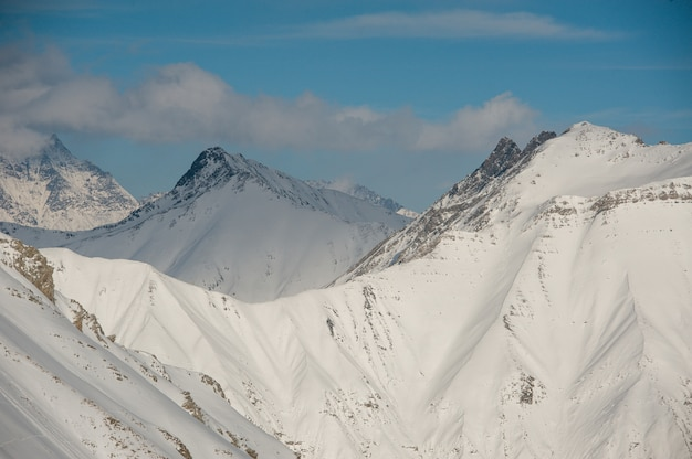 Wysokie czyste zimowe góry pokryte śniegiem pod jasnym błękitnym niebem