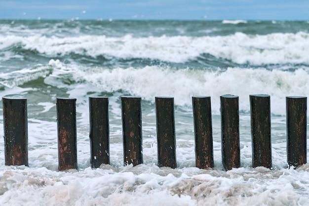Wysokie drewniane falochrony rozciągające się na wybrzeżu, widok z bliska. długie tyczki lub ostrogi w spienionych falach morskich. pochmurny i burzliwy dzień na morzu.
