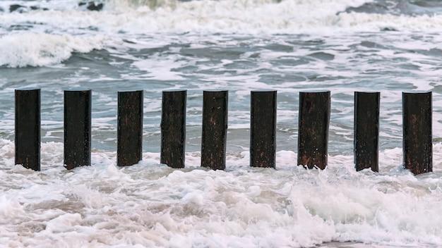 Wysokie drewniane falochrony w niebieskich fal morskich pieniących się, widok z bliska. długie kije lub ostrogi w wodzie. burzliwy dzień na morzu.