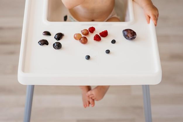 Wysokie dziecko w krzesełku wybiera owoce do jedzenia