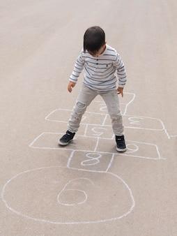 Wysokie dziecko widok gra w klasy na ulicy