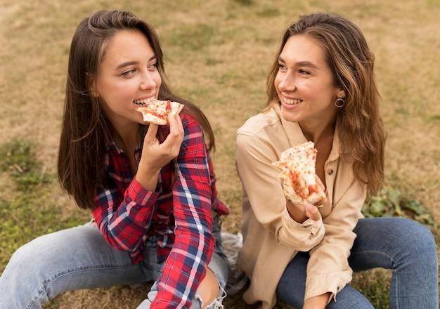 Wysokie dziewczyny jedzą pizzę