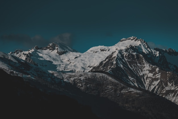 Wysokie góry pokryte wieczorem śniegiem