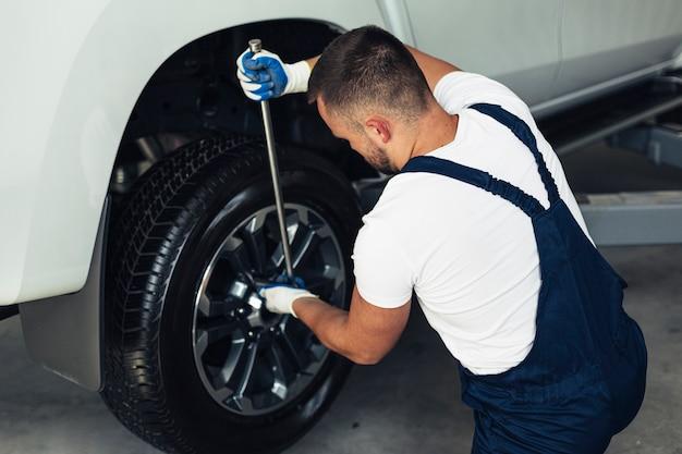 Wysokie kąty męskich mechanik zmienia koła samochodu