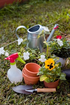 Wysokie kąty narzędzia ogrodnicze i kwiaty na ziemi