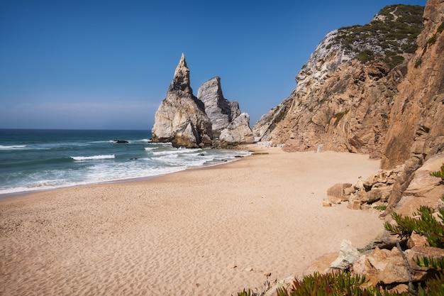 Wysokie klify na plaży praia da ursa, sintra, portugalia