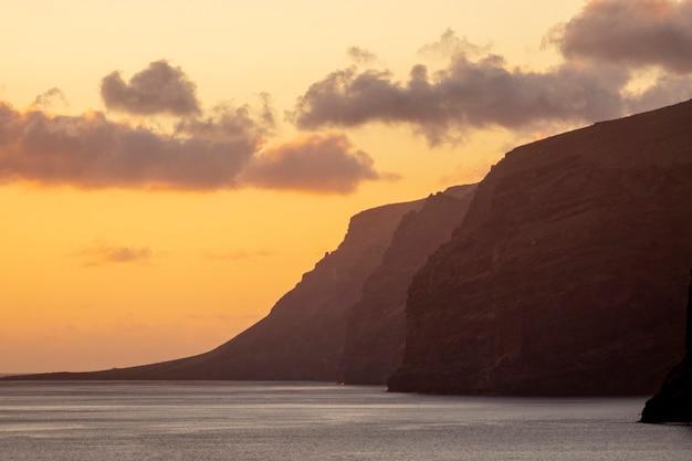 Wysokie klify nad morzem o zachodzie słońca