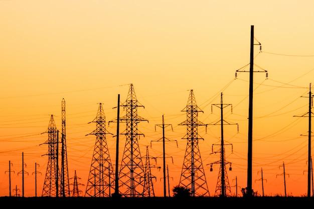 Wysokie napięcie linii energetycznych o zachodzie słońca