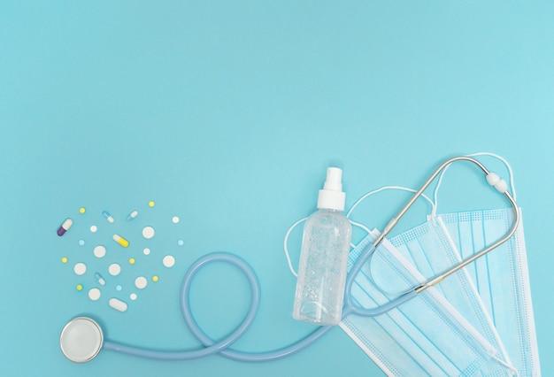 Wysokie niebieskie tło z widokiem z góry z antyseptycznym sprayem stetoskopowym i pigułkami