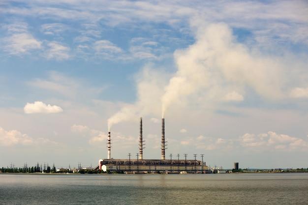 Wysokie rury elektrowni cieplnej z gęstym dymem odbijającym się w powierzchni wody. zanieczyszczenie środowiska.