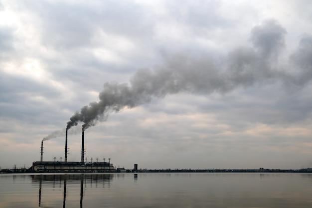 Wysokie rury elektrowni węglowej z czarnym dymem unoszące się w górę, zanieczyszczające atmosferę z jej odbiciami w wodzie jeziora.