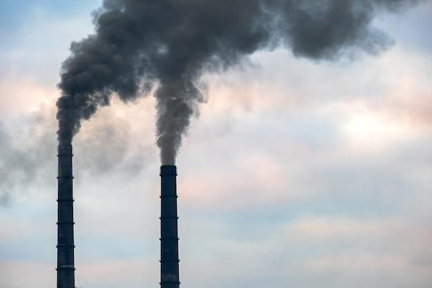 Wysokie rury elektrowni węglowej z czarnym dymem unoszącym się w górę zanieczyszczającej atmosfery.