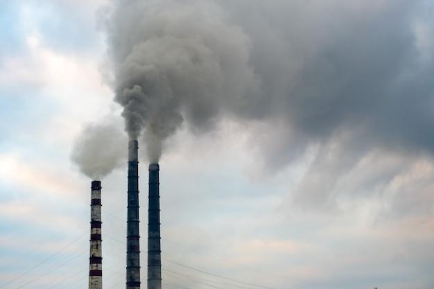 Wysokie rury elektrowni węglowej z czarnym dymem w górę zanieczyszczającej atmosfery.