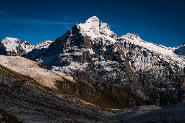 Wysokie skaliste góry pokryte śniegiem pod jasnym, błękitnym niebem w szwajcarii