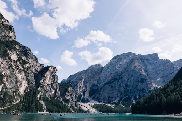 Wysokie skaliste góry wokół górskiego jeziora. lago di braies. dolomity, włochy.