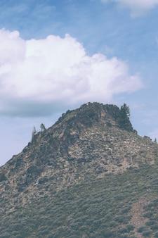 Wysokie skaliste wzgórze z dużymi chmurami na niebieskim niebie
