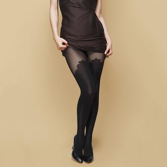 Wysokie szczupłe kobiece nogi w rajstopach. rajstopy z nadrukami.