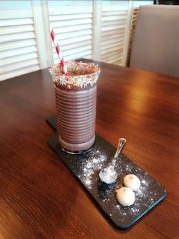 Wysokie szkło z koktajlem czekoladowym lub frappe kawy na desce do serwowania na stole w kawiarni.