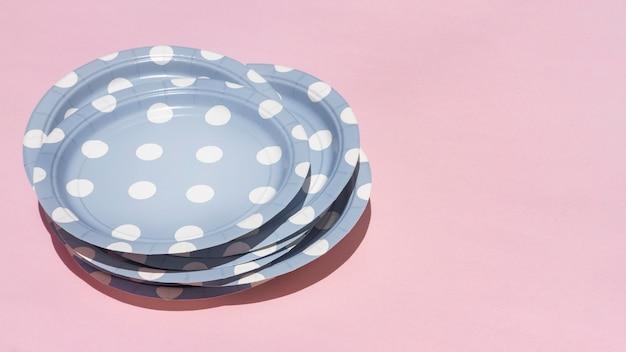 Wysokie talerze na różowym tle