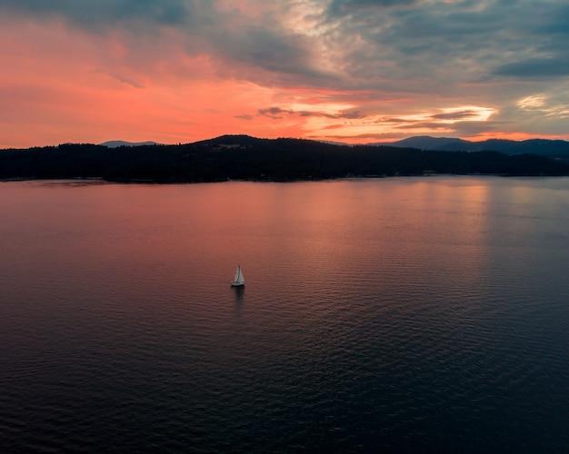 Wysokie ujęcie pięknego morza z pojedynczą łodzią płynącą o zachodzie słońca