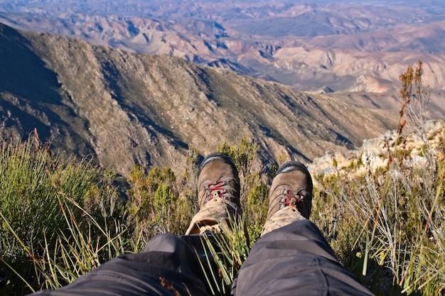 Wysokie ujęcie przedstawiające stopy osoby siedzącej na szczycie wzgórza nad piękną doliną