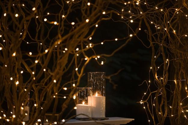 Wysokie wazony z białymi świecami stoją pod błyszczącymi gałęziami