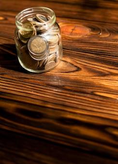 Wysokie widok monety w słoju na drewnianym tle