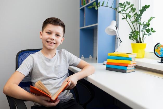 Wysokiego kąta chłopiec na krześle z książką