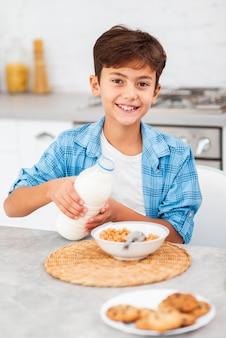 Wysokiego kąta chłopiec nalewa mleko na zbożach